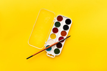 top view of brush and paints on yellow