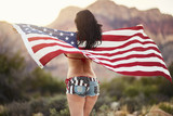 patriotic girl in bikini and sexy shorts holding american flag blowing in the wind - 151215652