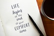 Quadro LIFE BEGINS AT THE END OF YOUR COMFORT ZONE written in brush calligraphy on notepad