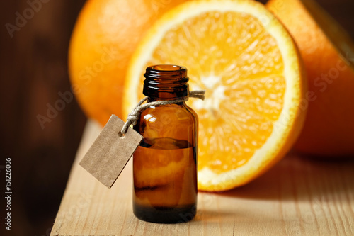 Orange essential oil in a glass bottle on a wooden table