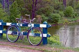 Старый велосипед возле ограждения на берегу водоёма