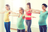 happy pregnant women exercising in gym