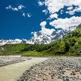 Summer mountain landscape with small rough river against snowy mountains and blue sky. Russian Caucasus, Elbrus region.