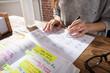 Businesswoman Marking Schedule On Calendar - 151302638