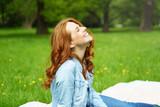 frau sitzt draußen im grünen und lacht - 151323455