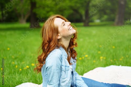 Kobieta siedzi na zewnątrz w zieleni i się śmieje