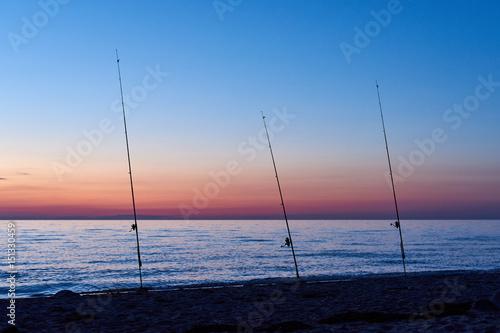 Drei Angelruten am Strand in der Dämmerung Poster