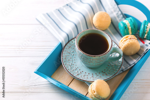 Cup of coffee and macaron cakes on tray Poster