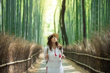 Asian woman tourist enjoy traveling into Arashiyama bamboo forest in Kyoto, Japan.