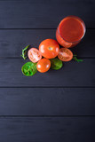 Fresh tomato juice in a glass with tomatoes and greens on a black wooden background. Space for text.