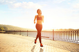 Woman running by the lake at sunset. Sport and lifestyle concept