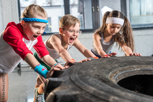 adorable kids in sportswear training with tire at fitness studio, children sport concept