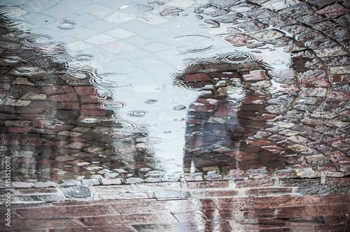 Juliste reflet dans une flaque d'eau d'un couple marchant avec un parapluie sur un place