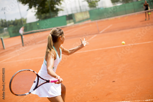 Plexiglas Tennis Pretty female tennis player playing on court on a sunny day