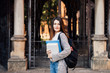 Portrait of a happy female student holding books and looking at camera outdoors near University