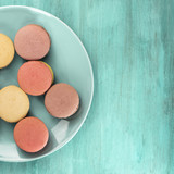 Photo of macarons on teal blue plate with copyspace