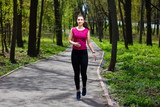 Young pretty fit woman jogging in the park.