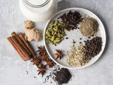 Ingredients for masala tea - milk, cinnamon, cardamom, anise, fennel, ginger, black tea, star anise, black pepper, cloves on grey background. Top view