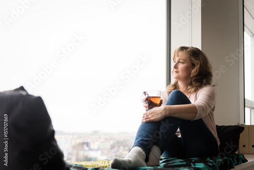 Senior woman drinking tea and looking through window - 151707869