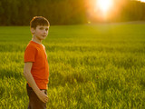 Portrait of an Young boy in the field on the sunset