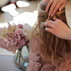 Mother pinch hair on little daughter's head. Hairdresser is Hairstyling young blonde girl in pink fluffy dress sitting near flovers bouquet. Getting ready for birthday party celebration