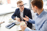 Fototapety Portrait of two business people talking at table in cafe smiling and gesturing actively discussing work