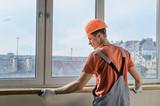 Worker is installing a window sill. - 151807867