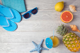 Tropical summer vacation background with pineapple, juice and flip flops on wooden table. View from above. Flat lay