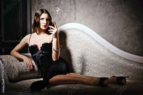 Poster Seductive young woman lying on sofa and smoking cigarette