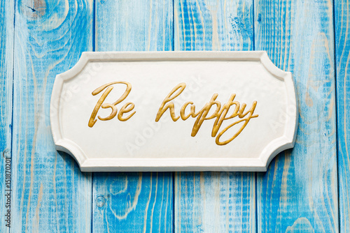 """A porcelain tile with """"Be happe"""" sign on the wooden background Poster"""