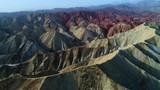 Flying a drone over the colorful Zhangye Rainbow Mountains; aerial view on sandstone hills and mountain chains covered by amazing pattern. Part 4 of a 5 part series-can be merged to 1 continuous movie - 151879602