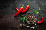 Red hot chili pepeprs and peppercorns on black metal background, top view