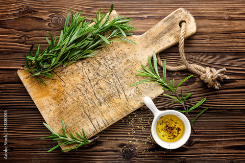 Culinary background with wooden board and cooking ingredients, olive oil and ros Poster