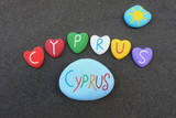 Cyprus, souvenir with multicolored stone hearts over black volcanic sand
