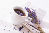 Cup of coffee with lavender flowers on table