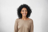 Fototapety Waist up portrait of cheerful young mixed race female with curly hair posing in studio with happy smile. Dark-skinned woman dressed casually smiling joyfully, showing her white straight teeth