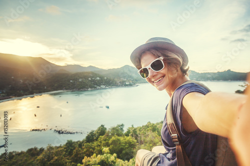 young woman traveler in sunglasses makes selfie with sea view