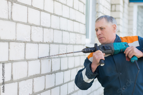 Foto op Plexiglas Wand An adult gray-haired male builder drills a white brick wall with a perforator