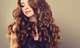 Fototapety Brunette  girl with long  and   shiny wavy hair .  Beautiful  model with curly hairstyle .