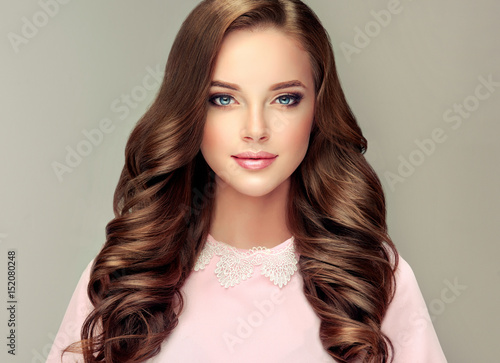 Brunette  girl with long  and   shiny wavy hair .  Beautiful  model with curly hairstyle .  © Sofia Zhuravetc