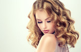 Beautiful blonde model girl with curly hair .Young woman with short wavy hairstyle