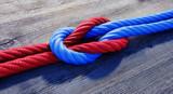 Kreuzknoten mit rotem und blauem Seil auf Holz - 152111897