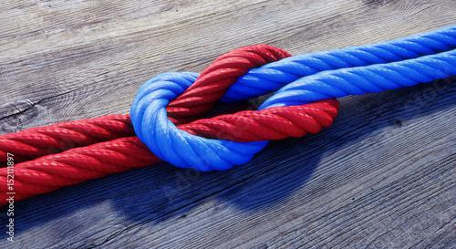 Leinwanddruck Bild Kreuzknoten mit rotem und blauem Seil auf Holz