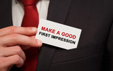 Businessman putting a card with text Make a good first impression in the pocket - 152145299