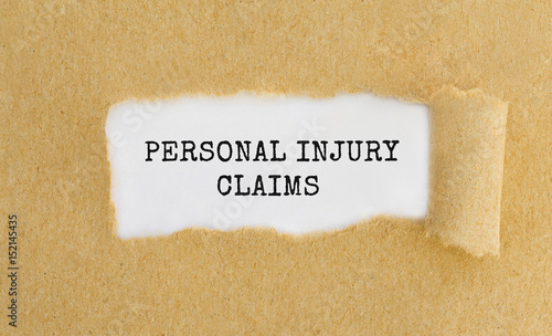 Text Personal Injury Claims appearing behind ripped brown paper