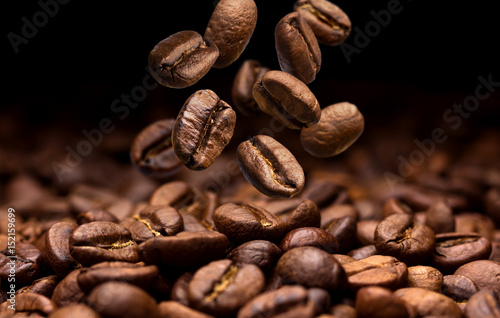 Falling coffee beans. Dark background with copy space, close-up