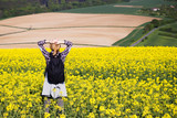 Young hiking woman is looking out over the countryside. Beautiful yellow rape field and rural landscape in the background.