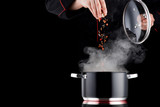 Modern chef in professional uniform adding spice to steaming pot - 152186264