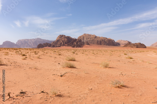 Great expansive of the Wadi Rum Desert with orange sand and rocky mountains in the distance Poster