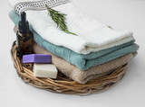 Spa towels still life on wicker tray with essential oil bottle and natural soap